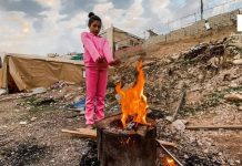 Salah satu anak dari keluarga Al-Maqdisi Fawaz Abdu tengah menghangatkan badan di depan api unggun. Foto/Palinfo
